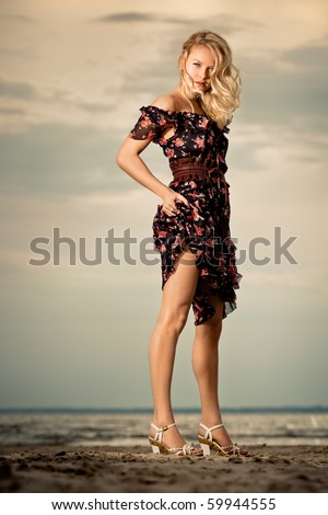Woman in a dress. A woman in a dress on the beach. - stock photo
