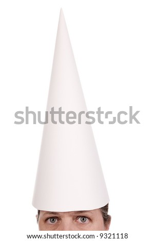 Woman in a dunce cap with eyes open over a white background - stock photo