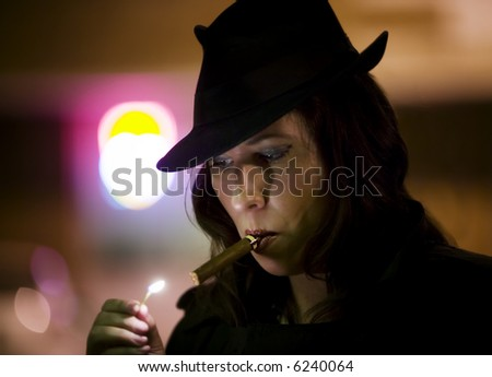Woman in a fedora lighting a cigar with a match. - stock photo