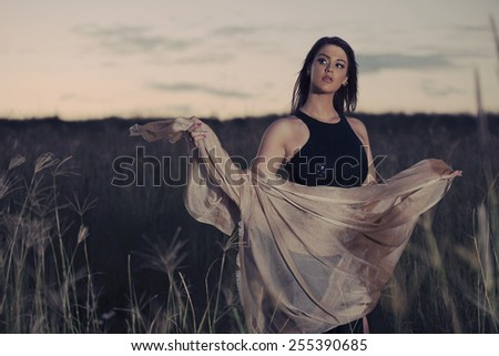 Woman in a field in the late afternoon posing while wearing a dress in Brisbane, Queensland.