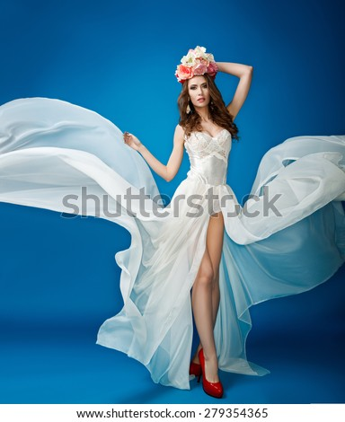 Woman in a flowing white dress with flowers on her head on a blue background