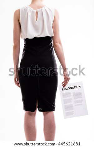 Woman in a formal black skirt standing with her back to the camera holding a resignation letter, torso view isolated on white - stock photo