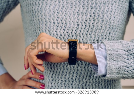 Woman in a gray sweater checks the time on a wrist watch close-up. - stock photo