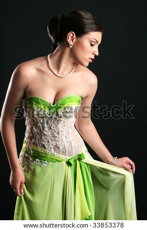 Woman in a green dress posing on a black background - stock photo