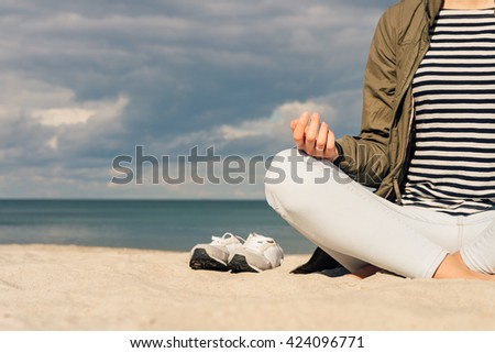 Woman in a green jacket and jeans sitting barefoot on the beach and meditating - stock photo