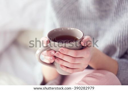 Woman in a grey sweater and warm socks holding a cup of tea while sitting on a white knitted blanket - stock photo