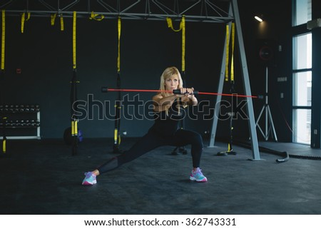 woman in a gym exercising. Dark background
