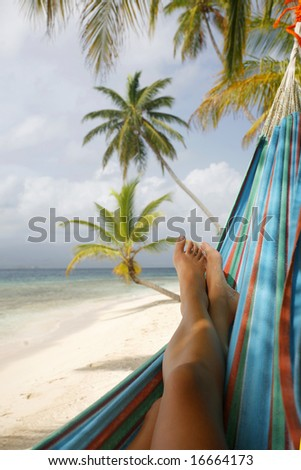 Woman in a hammock on a tropical beach - stock photo