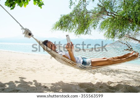 Woman in a hammock with laptop at the beach. Bali, Indonesia. Stock image. - stock photo
