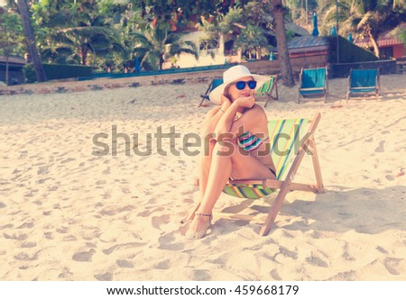 woman in a hat on a beach, sitting in a deck chair and watching the sea - stock photo