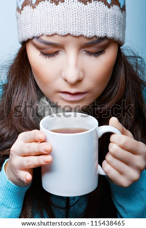 woman in a hat with hot tea closeup on a blue background