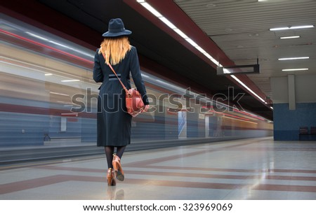 Woman in a hurry to walk the modern subway station tunnels - stock photo