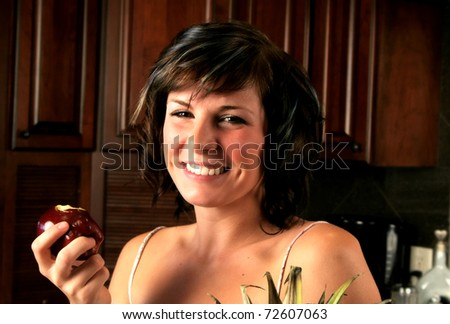 Woman in a kitchen eating an apple - stock photo