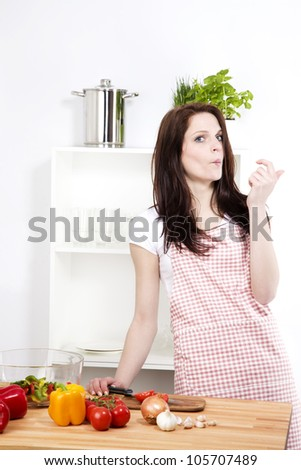 woman in a kitchen making faces instead of cutting her vegetables - stock photo