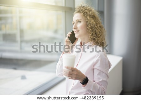 Woman in a light pink shirt standing at the window and talking on a cell phone,in hand a cup of coffee, on the wrist smartwatches.Selective focus,film effect, blurred background.