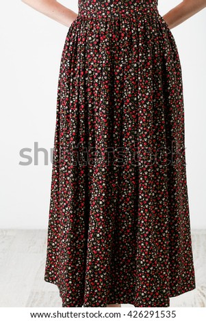 Woman in a long multicolor skirt on white background