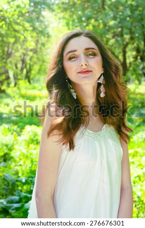 Woman in a long white dress standing in the sunny forest in summer. Smiling happily.