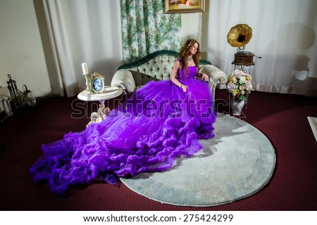 Woman in a luxury, long purple dress sitting on the couch - stock photo