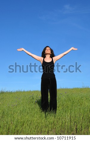 Woman in a meadow with arms outstretched - stock photo