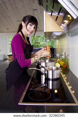 Woman in a modern kitchen stirring in the saucepan