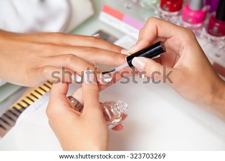 Woman in a nail salon receiving a manicure by a beautician - stock photo