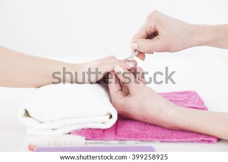 Woman in a nail salon receiving a manicure by a beautician.