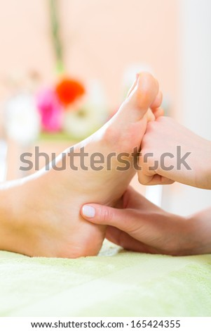 Woman in a nail salon receiving a pedicure by a beautician, she is getting a foot massage - stock photo