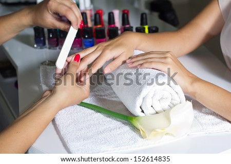 Woman in a nail salon receiving, maintenance of hygiene nails - stock photo