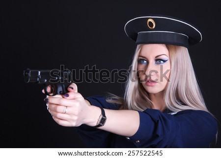 Woman in a navy uniform with a gun over black background - stock photo