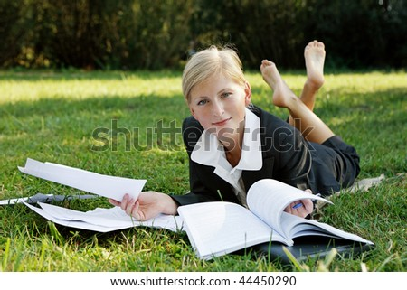 woman in a park engaged in paper cases - stock photo
