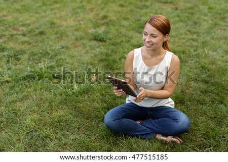 Woman in a park using tablet computer