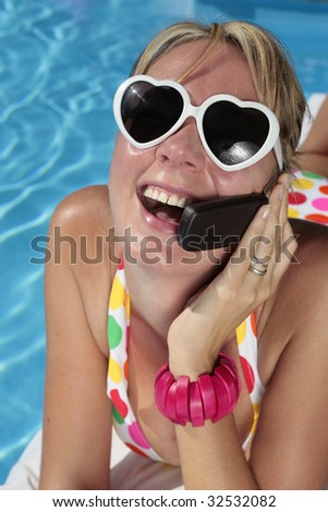 Woman in a polka dot bikini on her cellphone by a nice blue swimming pool - stock photo