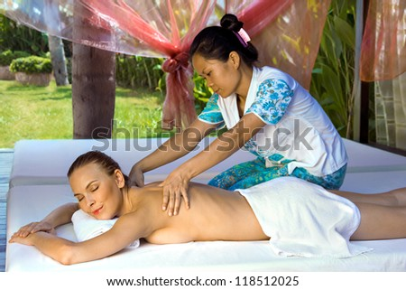 Woman in a prone position, getting a back massage from a thai masseuse inside a spa hut, grass and trees visible in the background. - stock photo