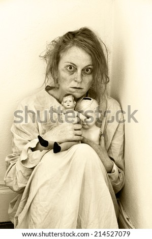 Woman in a psychiatric ward with two dolls. - stock photo