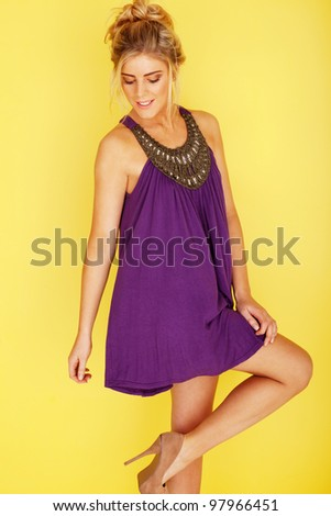 woman in a purple dress looking at her stilleto heels, her right knee slightly bent up, on a yellow background - stock photo