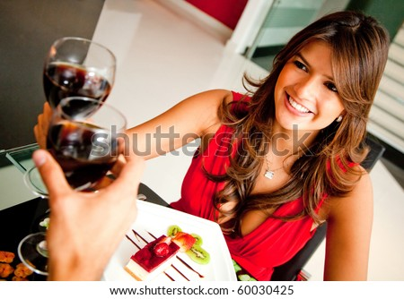 Woman in a romantic dinner toasting with wine - stock photo