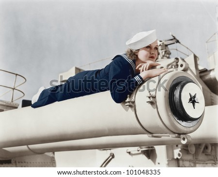 Woman in a sailors uniform lying on a cannon - stock photo