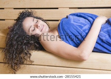 woman in a sauna with towel relaxing