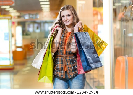 woman in a shopping mall holding shopping bags