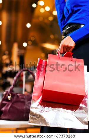 woman in a shopping mall with colorful bags - stock photo
