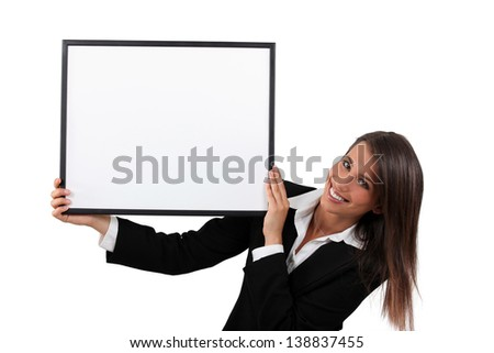 Woman in a smart black suit holding a board left blank for your image or message - stock photo