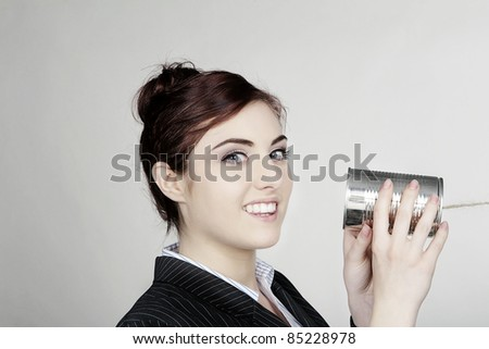 woman in a smart business suit in communication using a tin can and string