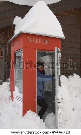 Woman in a snow-covered telephone booth - stock photo
