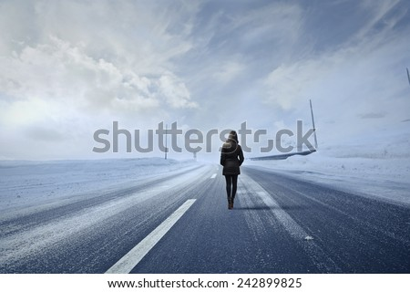 Woman in a snowy road  - stock photo