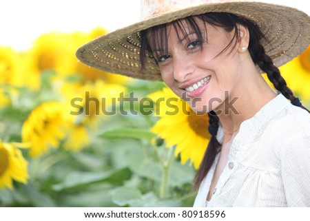 Woman in a straw hat in a sunflower field - stock photo