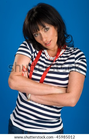 Woman in a striped shirt poses on a blue background - stock photo