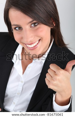 Woman in a suit giving the thumbs up - stock photo