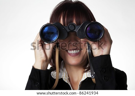 woman in a suit holding up binocular to her eyes