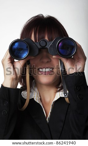 woman in a suit holding up binocular to her eyes - stock photo