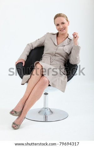 Woman in a suit sitting in a designer swivel chair - stock photo